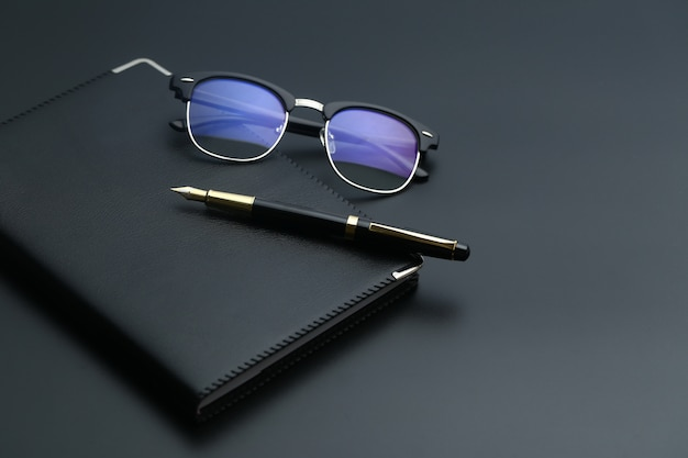 Gouden pen, notitieboekje, rekenmachine en glazen op zwart bureau