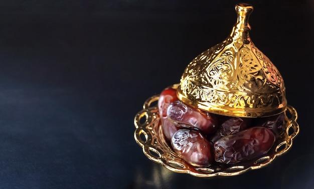 Gouden plaat met gedroogde dadelpalmvruchten of kurma. ramadan kareem-concept.