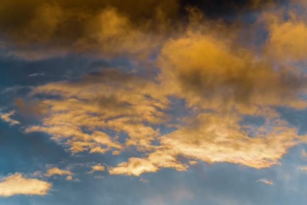 Gouden pluizige wolken verlicht door verdwijnende stralen bij zonsondergang en donkere onweerswolken blauwe lucht