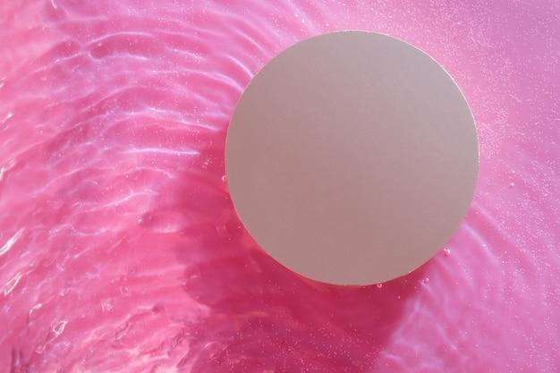 Gouden podium bovenaanzicht onder kleurenwatergolven voor product- en cosmetische presentatie. minimaal water achtergrondconcept