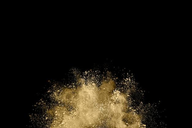 Gouden poederexplosie op zwarte achtergrond.