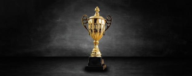Gouden prijs en trofee in donkere en zwarte studio en showroom