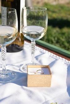 Gouden ring en wijnglazen als esthetiek van het voorstel in de tuin