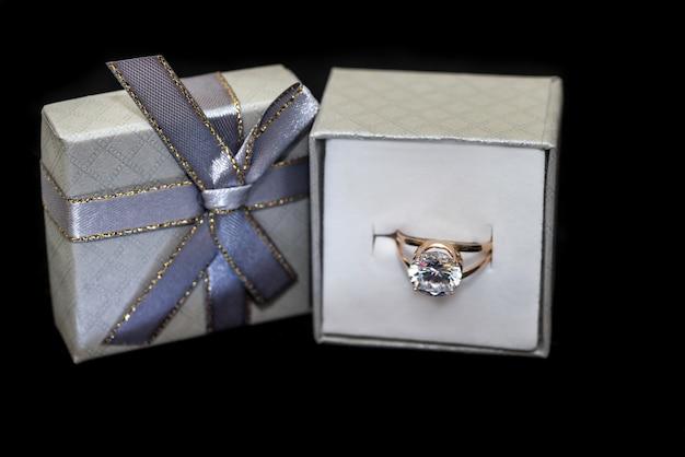 Gouden ring met diamant in doos geïsoleerd op zwart oppervlak