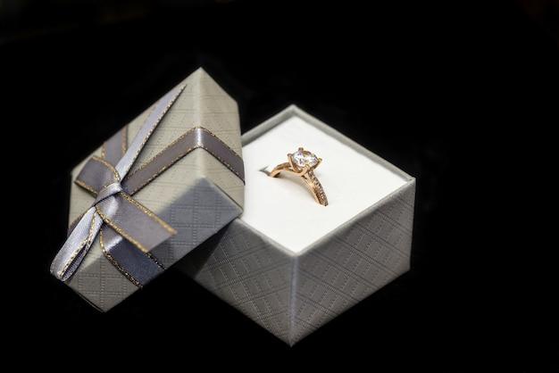 Gouden ring met diamant in doos geïsoleerd op zwart