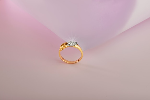 Gouden ring met diamanten op een roze achtergrond