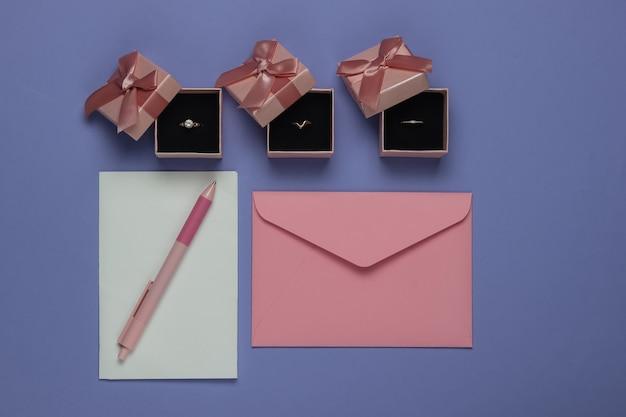 Gouden ringen in een geschenkdozen, envelop met huwelijksuitnodigingen op paarse achtergrond. bovenaanzicht. plat leggen