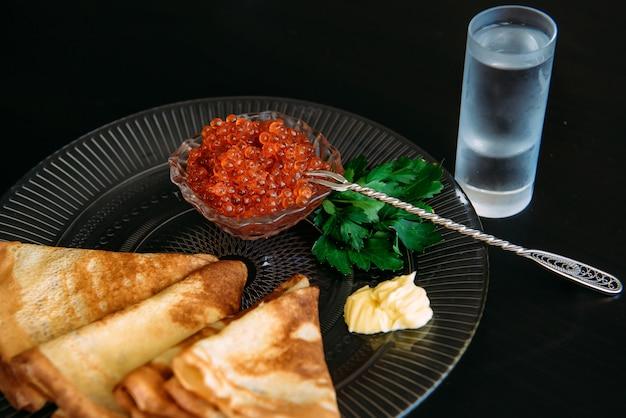 Gouden russische pannenkoeken met rode kaviaar en boter in transparante plaat in de buurt van het glas ijs wodka