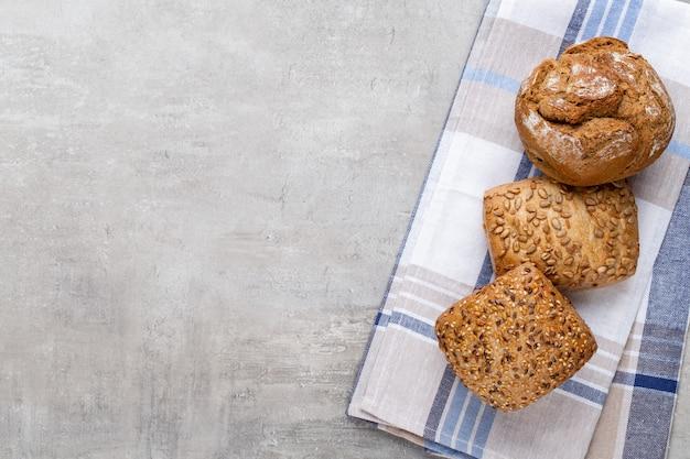 Gouden rustieke knapperige broden en broodjes op houten achtergrond. stilleven gevangen van bovenaf gezien, plat gelegd.