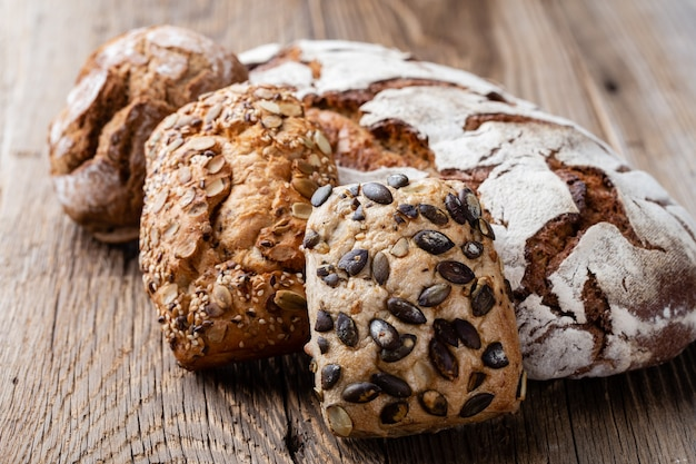 Gouden rustieke knapperige broden en broodjes op houten achtergrond. stilleven vastgelegd van bovenaf, plat gelegd.