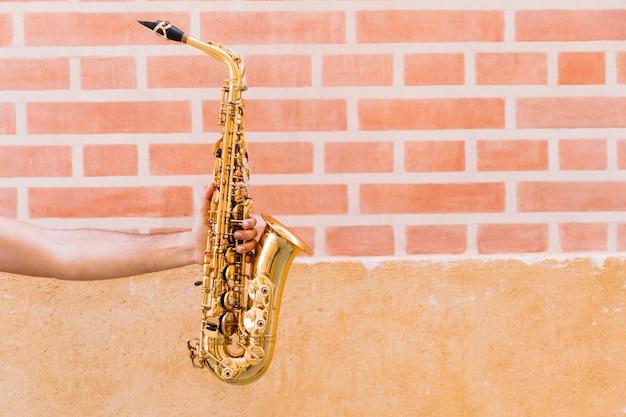 Gouden saxofoon die door de mens wordt gehouden
