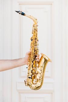 Gouden saxofoon die door persoon wordt gehouden