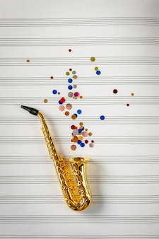 Gouden saxofoon met gekleurde lovertjes op de achtergrond van het muzieknotitieboek. jazz dag concept.