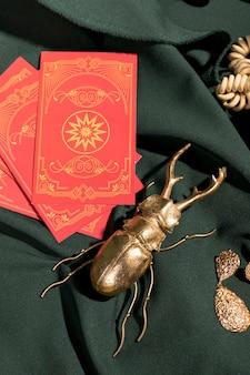 Gouden scarabee naast rode tarotkaarten