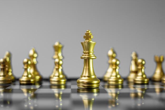 Gouden schaakfiguurteam (koning, dame, loper, paard, toren en pion) op schaakbord tegen tegenstander tijdens gevecht.