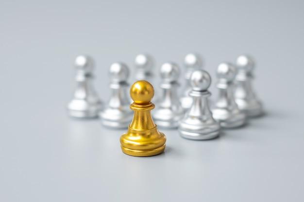 Gouden schaakpionstukken of leiderzakenman vallen op in de menigte mensen van zilveren mannen. leiderschap, business, team, teamwork en human resource management concept