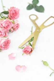 Gouden schaar en roze rozen