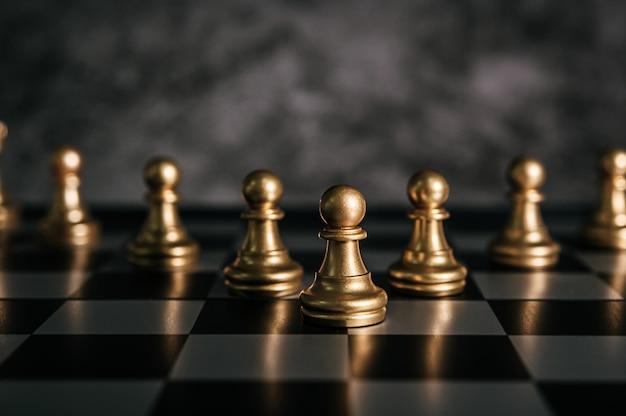 Gouden schaken op schaakbordspel voor bedrijfsconcept metafoor leiderschap