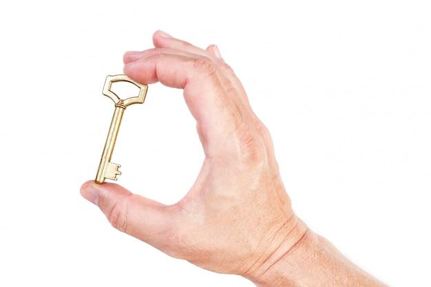 Gouden sleutel in hand symbool van het rijke huis. op een witte muur.