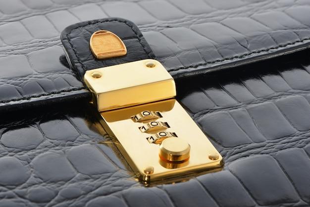 Gouden slot combinatie op zwart leren tas. luxe accessoires.