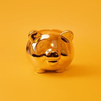 Gouden spaarvarken op gele achtergrond, geldbesparing, spaarpot