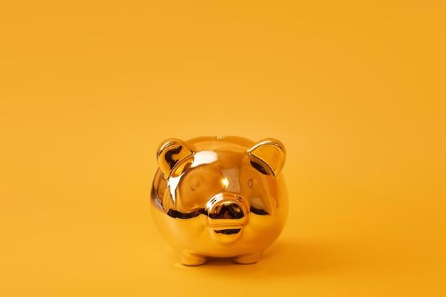 Gouden spaarvarken op gele achtergrond. gouden spaarpot. geldvarken, geldbesparing, spaarpot, financiën en investeringen concept. vrije ruimte voor tekst.