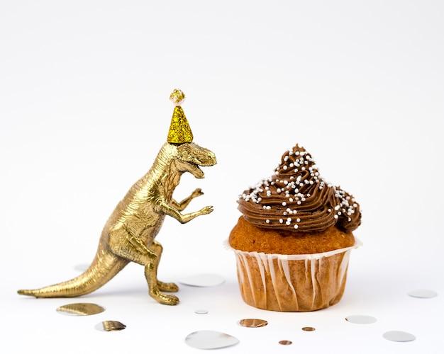 Gouden speelgoed dinosaurus en smakelijke muffin
