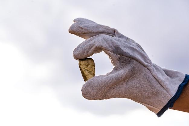Gouden stenen close-up in de hand van een mijnbouwbedrijf met handschoen. mijnbouw exploratie concept.