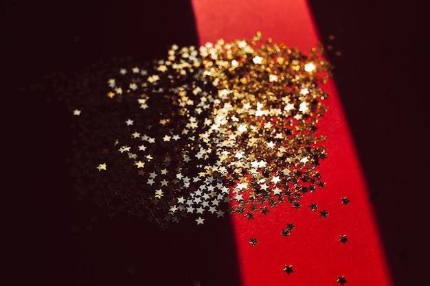 Gouden sterconfettien in ruw licht met schaduw
