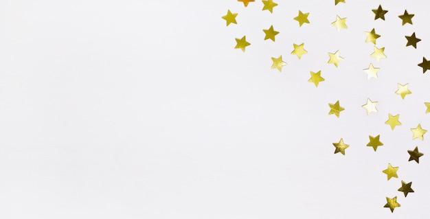 Gouden sterconfettien op witte houten grens