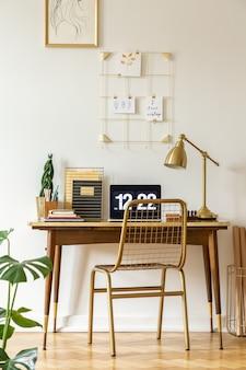 Gouden stoel aan bureau met laptop en lamp in klassiek freelancer's interieur. echte foto