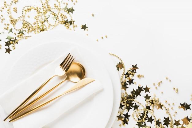 Gouden tafel instelling met glanzende sterren en kralen op wit.