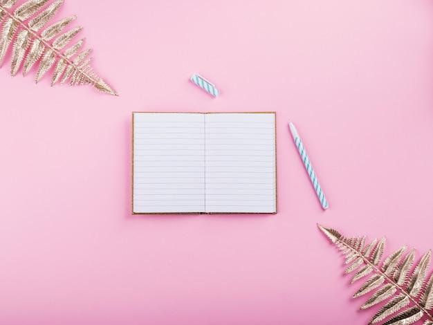 Gouden takken en notitieblok openen op roze