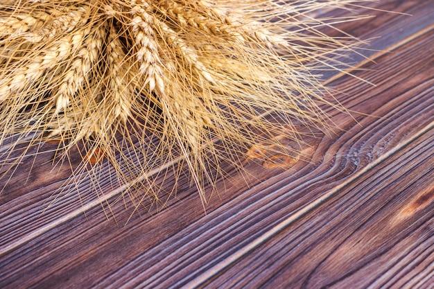Gouden tarwe die op een bruine houten oppervlakte ligt