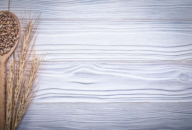 Gouden tarwe en rogge oren houten lepel graan op houten bord