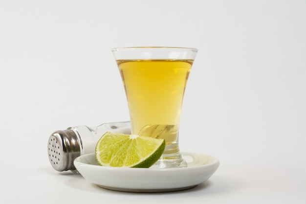Gouden tequila die op het witte oppervlak is ontsproten
