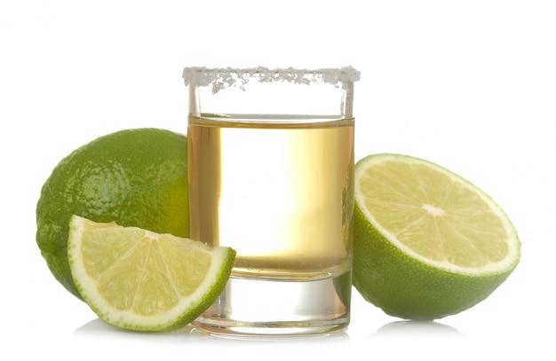 Gouden tequila in een glas met kalk dichte omhooggaand op een wit geïsoleerde achtergrond