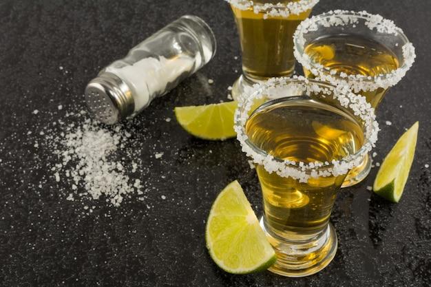 Gouden tequilaschoten met kalk op zwarte achtergrond