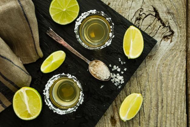 Gouden tequilaschoten op rustiek hout