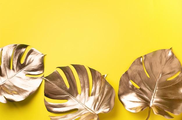 Gouden tropisch monsterablad op gele achtergrond met exemplaarruimte.