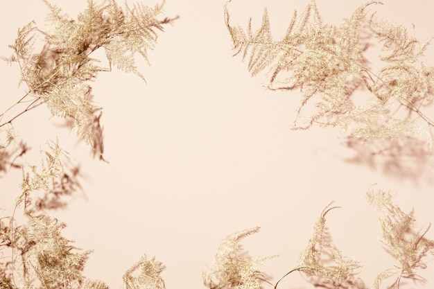 Gouden tropische bladeren op beige achtergrond. plat lag, bovenaanzicht.