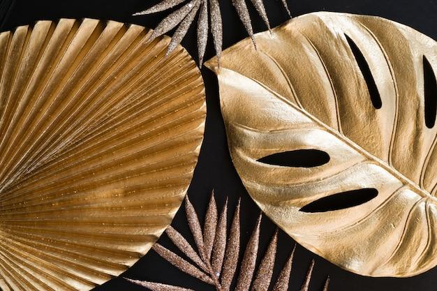 Gouden tropische bladeren op zwarte achtergrond, bovenaanzicht close-up