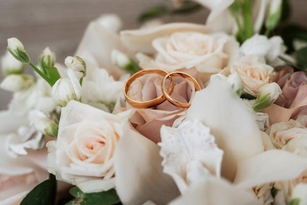 Gouden trouwringen als attribuut van de bruiloft van een jong stel