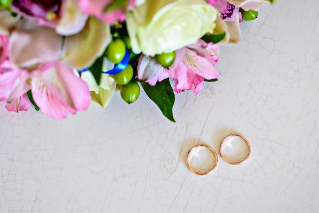 Gouden trouwringen en bruids boeket op een witte tafel