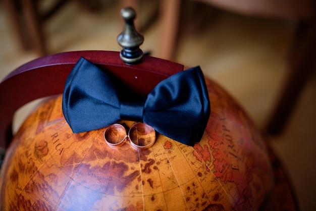 Gouden trouwringen en donkerblauwe vlinderdas liggen op de houten wereldbol