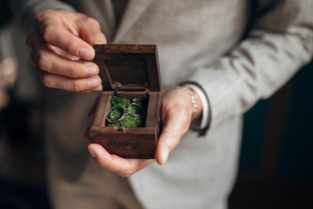 Gouden trouwringen in de handen van de bruidegom