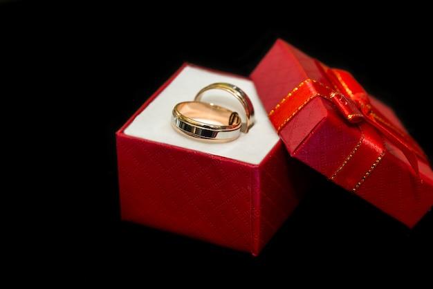 Gouden trouwringen in rode huidige doos op zwarte achtergrond