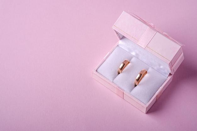 Gouden trouwringen in roze geschenkdoos op zachte roze achtergrond, hoekmening, kopie ruimte