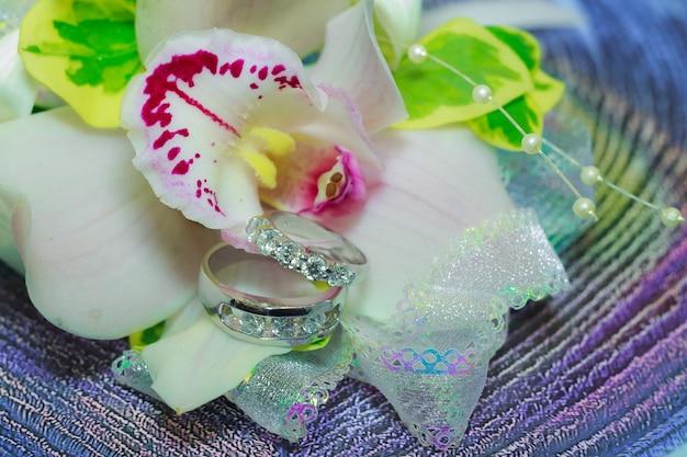 Gouden trouwringen liggen in leliebloem in het boeket. huwelijksboeket op vensterbank. traditionele symbolische accessoire van de bruid. symbool van liefde en huwelijk.