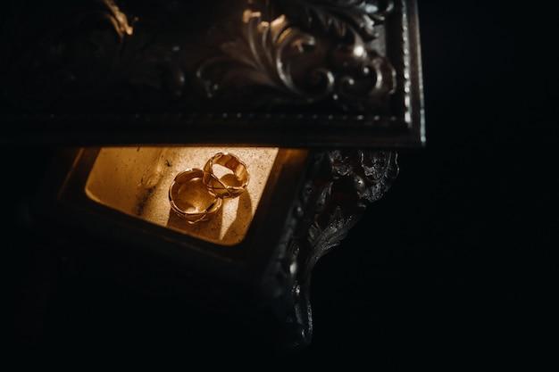 Gouden trouwringen liggen op een antiek juwelendoosje. trouwringen voor ceremonies.